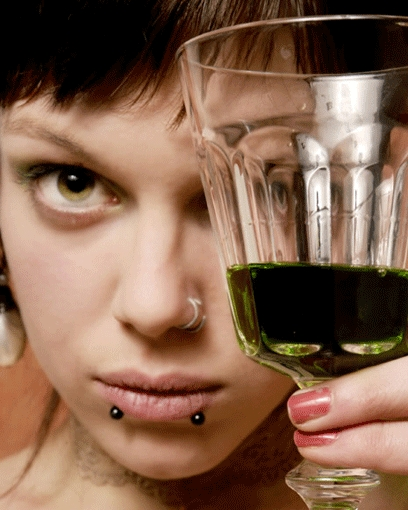 Woman_holding_up_glass_of_green_liquid