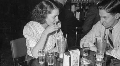 Boy and girl sitting at table at soda shop